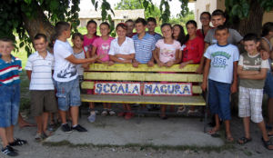 The school children proudly display the Mãgura School mosaic